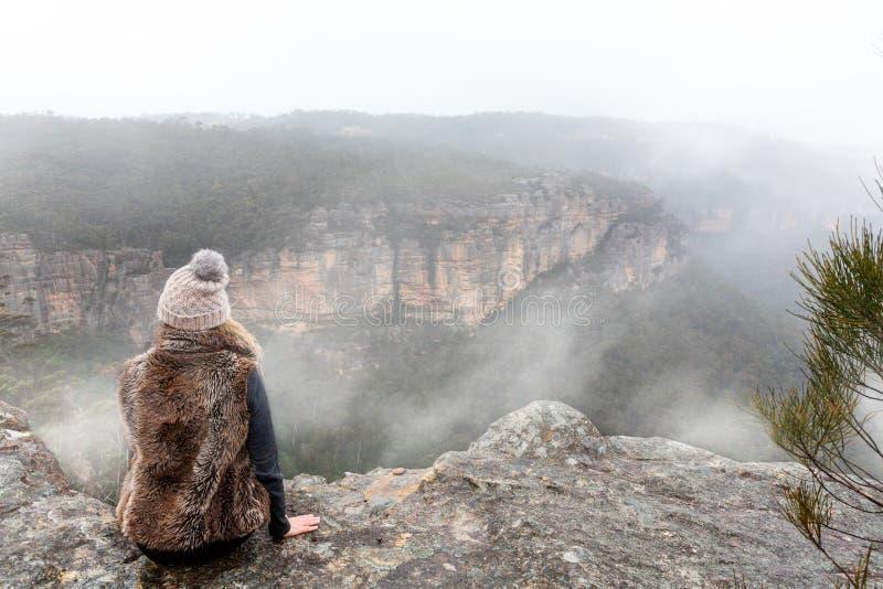 Vrouwelijke zitting op richel die van de berg de hoogste klip uit in de nevelige mist kijken stock foto's