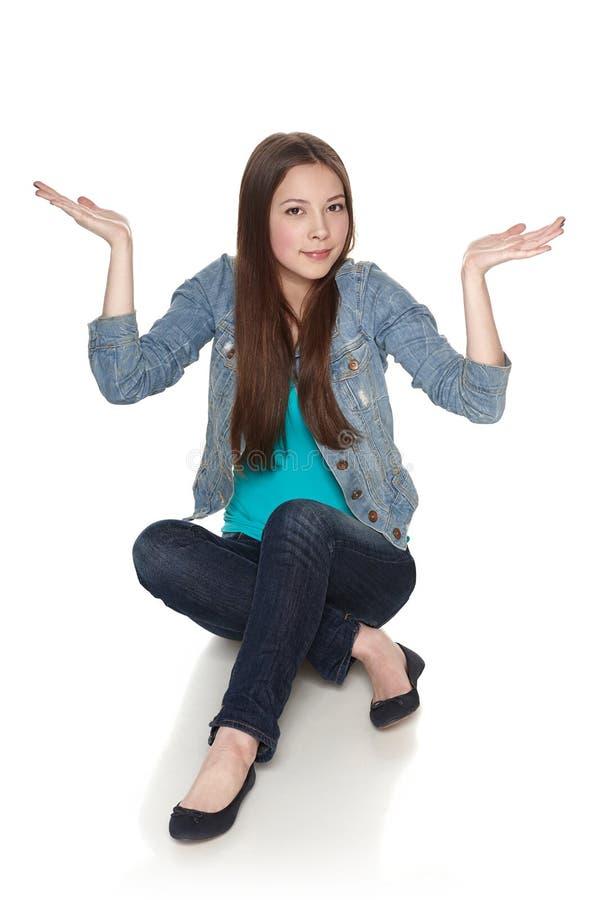 Vrouwelijke zitting op vloer die exemplaarruimte hierboven tonen stock foto's