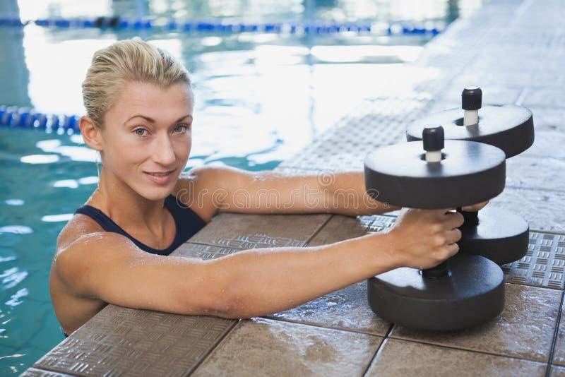 Vrouwelijke zwemmer met schuimdomoren in zwembad stock fotografie