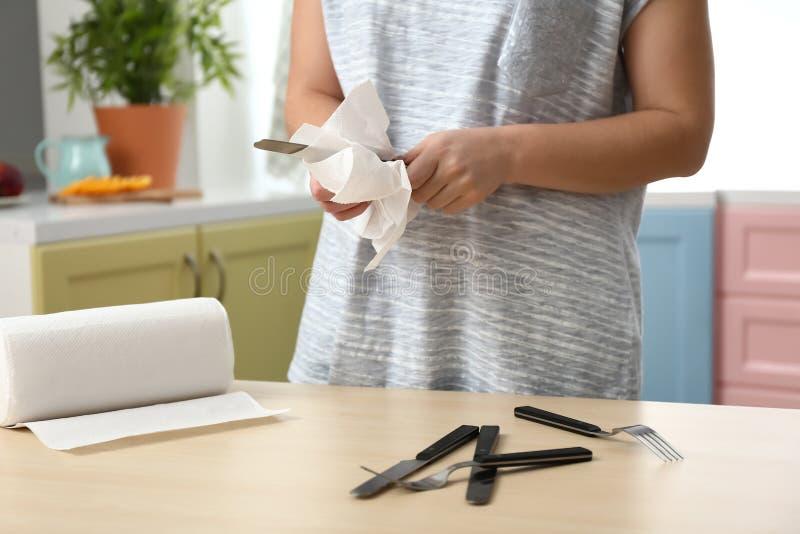 Vrouwen afvegend mes met keukenrol in keuken stock foto