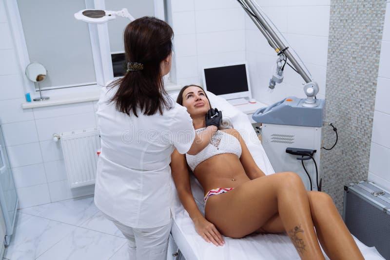 Vrouwen arts in kliniek Mooie vrouwelijke gezicht en cosmetologist` s handen met spuit tijdens gezichtsschoonheidsinjecties stock fotografie