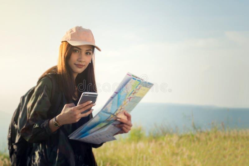Vrouwen Aziaat die met heldere rugzak een kaart bekijken Mening van bac stock foto