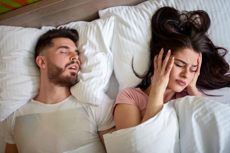 Vrouwen in bed die met echtgenoot snurken stock afbeeldingen