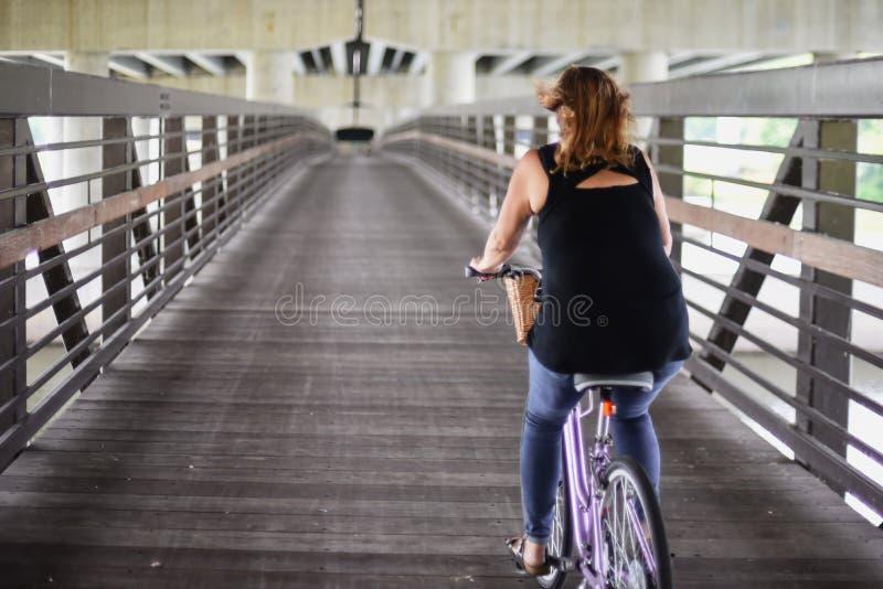 Vrouwen berijdende fiets op brug onder weg in stad royalty-vrije stock afbeelding