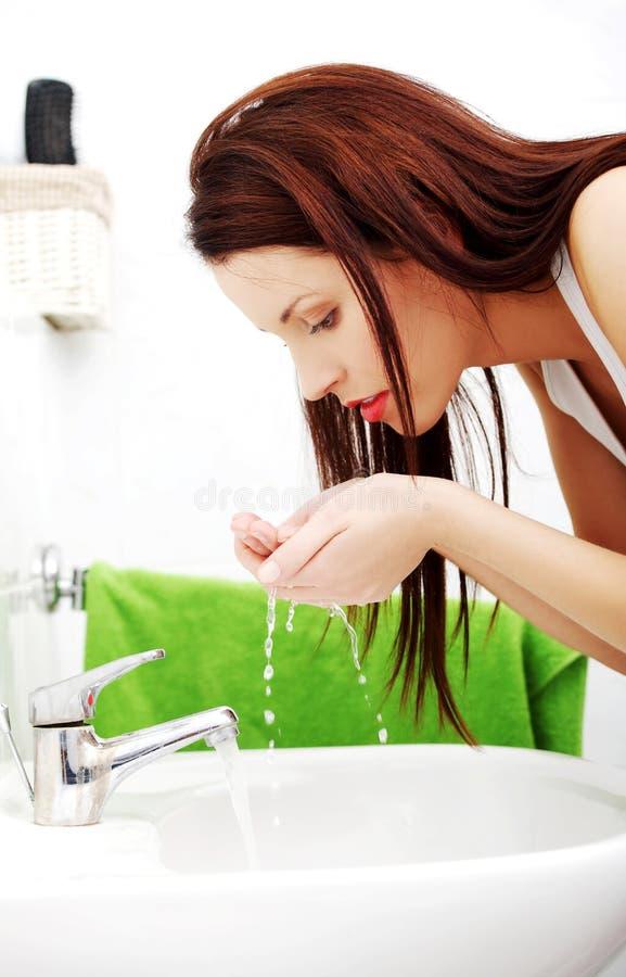 Vrouwen bespattend gezicht met water royalty-vrije stock afbeelding