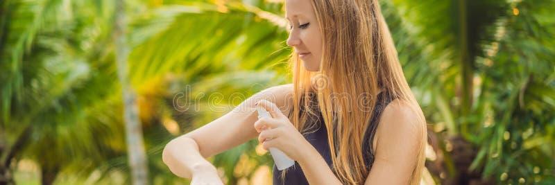 Vrouwen bespuitend insektenwerend middel op huid openluchtbanner, lang formaat stock afbeelding