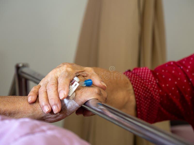 Vrouwen bezoekende echtgenoot in het ziekenhuis De hogere handen van de paarholding op het ziekenhuisbed voor ziekenhuisopname vo stock fotografie