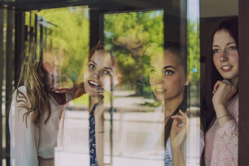 Vrouwen bij het venster die iets door het glas bekijken stock foto's