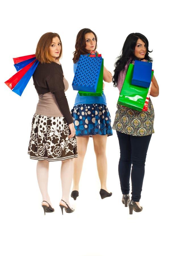 Vrouwen bij het winkelen terug lopend en kijkend stock afbeeldingen