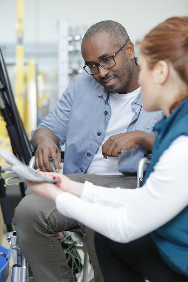 Vrouwen bijwonende man in rolstoel in ijzerhandel stock foto's