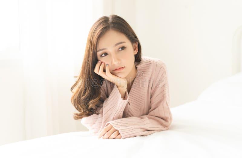 Vrouwen binnenportret Close-up van peinzende jonge Asain-vrouw in warme gebreide roze kleren in de slaapkamer Negatieve menselijk royalty-vrije stock afbeeldingen
