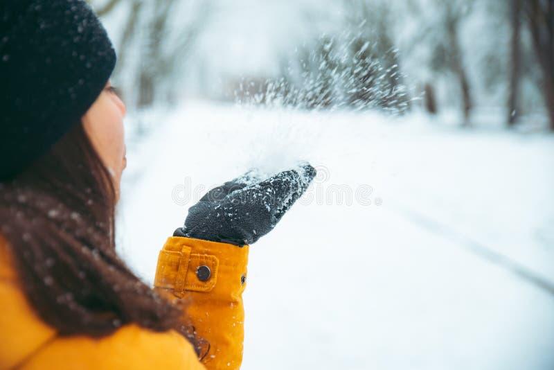 Vrouwen blazende sneeuw van haar handen gesneeuwd park op achtergrond Uren en landschap royalty-vrije stock foto's