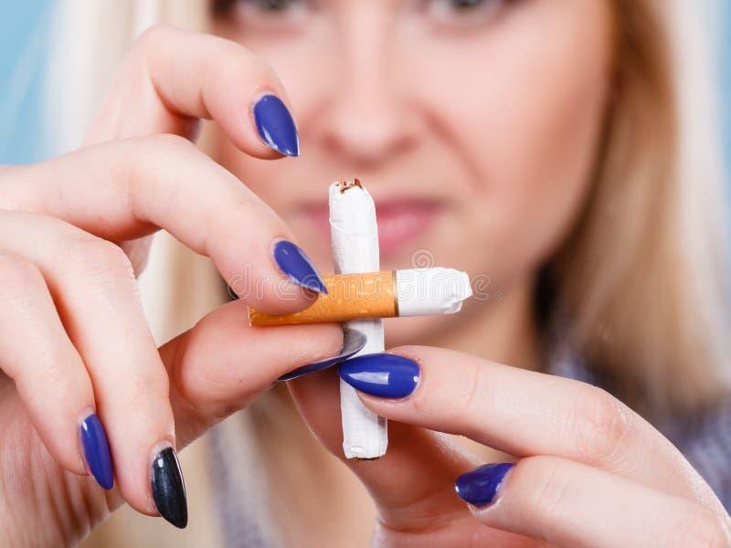 Vrouwen brekende sigaret, van de hand doende verslaving stock afbeeldingen