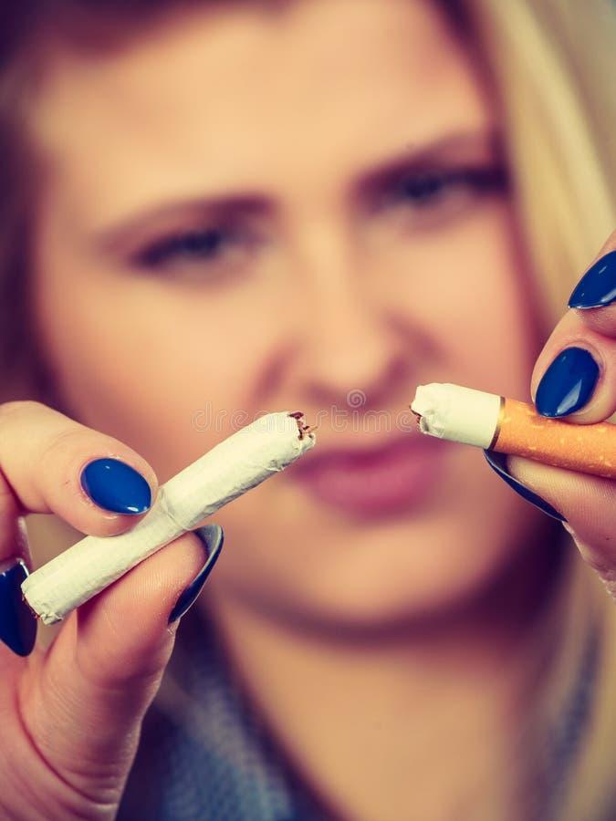 Vrouwen brekende sigaret, van de hand doende verslaving stock afbeelding
