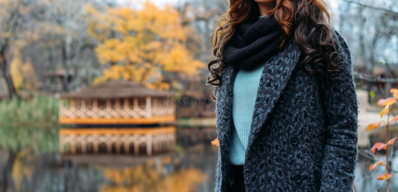 Vrouwen bruin-haired vrouw in een grijze laag, een blauwe sweater en een zwarte sjaal, snod de herfst, gebreide dingen, met de ha stock foto's