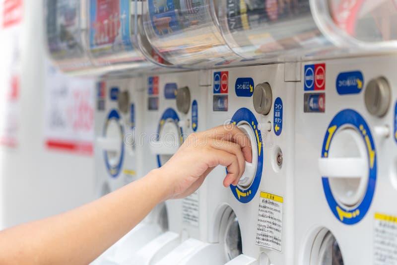 Vrouwen in de gashapon- of capsulemachine brengen munt in bij de Japanse verkoopautomaat voor capsule speelgoed Gachapon royalty-vrije stock afbeeldingen
