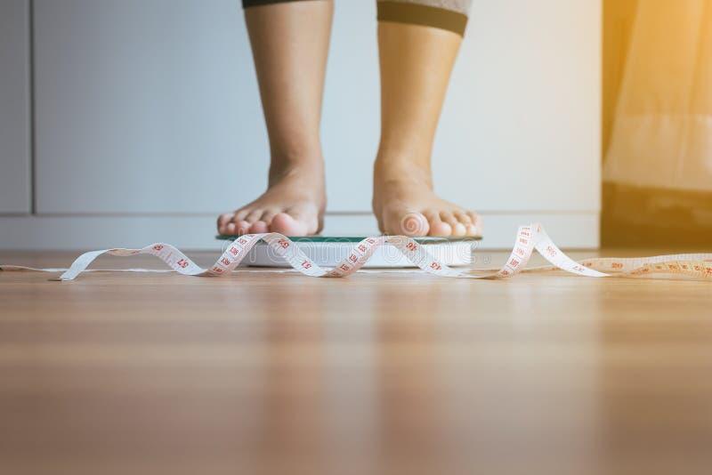 Vrouwen de voet die zich weegt schalen met meetlint in voorgrond, Gewichtsverlies bevinden royalty-vrije stock fotografie