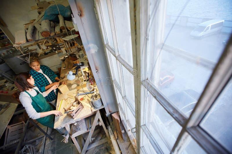 Vrouwen dichtbij werkbank in timmermansworkshop royalty-vrije stock foto's
