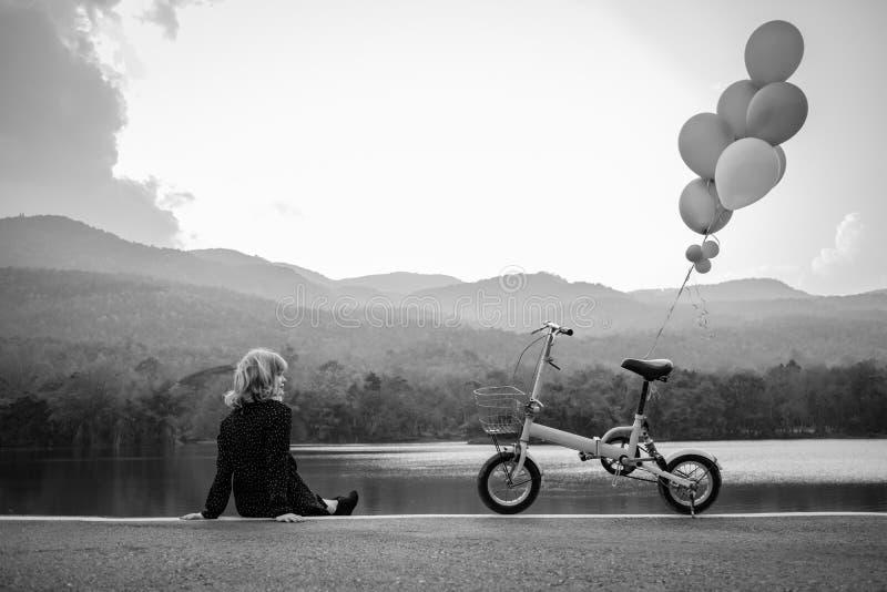 Vrouwen die alleen op de weg zitten die op liefde, alleen concept wachten stock foto