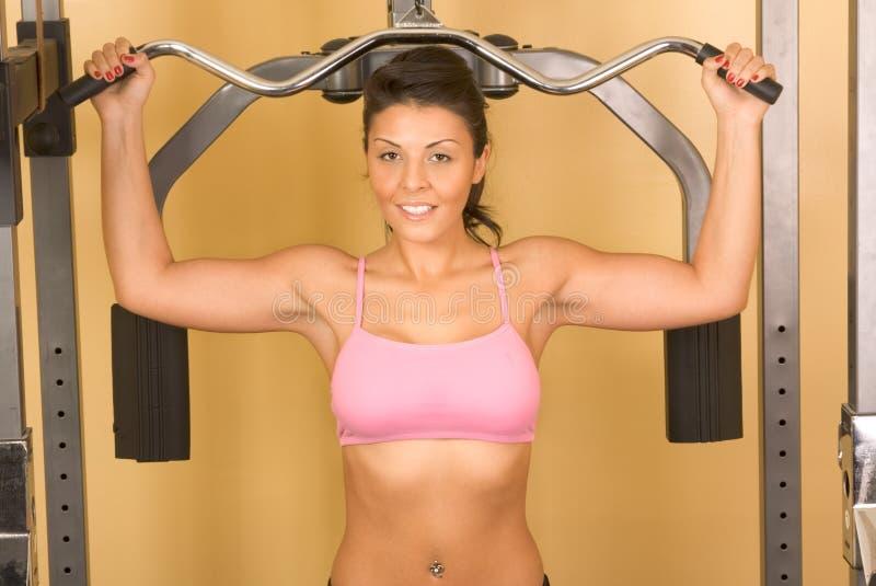 Vrouwen die bij het weightlifting van machine uitoefenen royalty-vrije stock afbeeldingen
