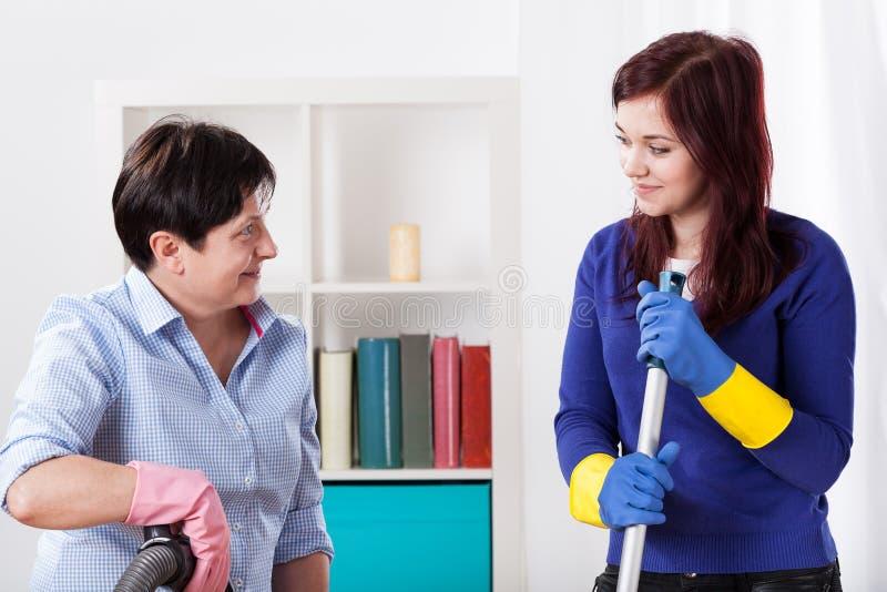 Vrouwen die bij huis schoonmaken stock foto's