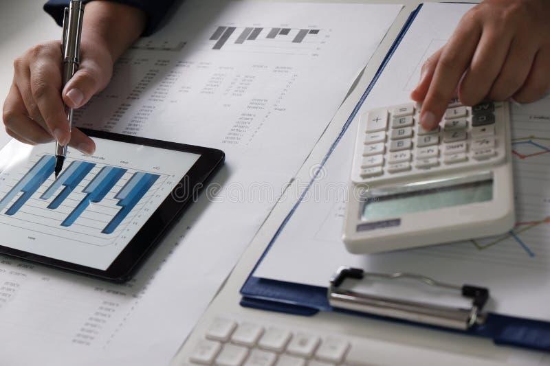 Vrouwen die in bureau werken financiële analyse met grafieken op tablet voor bedrijfs, boekhoudings, verzekerings of financiëncon stock foto's