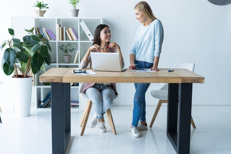 Vrouwen die, bureaubinnenland samenwerken Twee vrouwelijke collega's in bureau royalty-vrije stock afbeeldingen