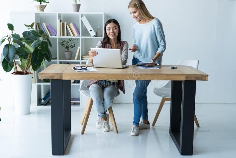 Vrouwen die, bureaubinnenland samenwerken Twee vrouwelijke collega's in bureau stock afbeeldingen