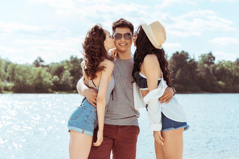 Vrouwen die de glimlachende mens op strand op de zomerdag kussen royalty-vrije stock afbeeldingen