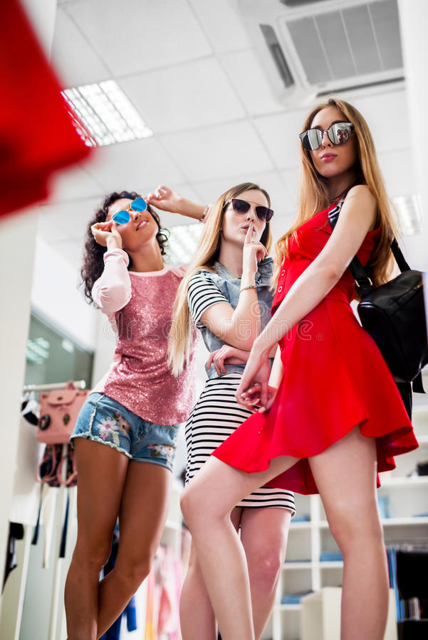 Vrouwen die de nieuwe inzameling van de dameszomer van kleren en toebehoren proberen die in spiegel in kledingsopslag kijken stock foto