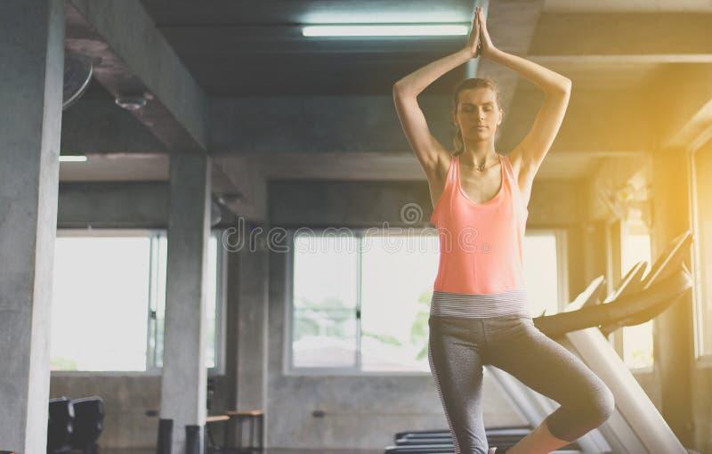 Vrouwen die doend de training van de yogaoefening na in gymnastiek, Gezonde en levensstijlconcept praktizeren royalty-vrije stock afbeelding