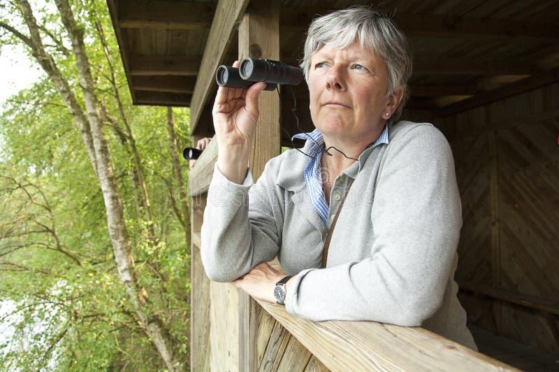 Vrouwen die door verrekijkers kijken stock afbeelding