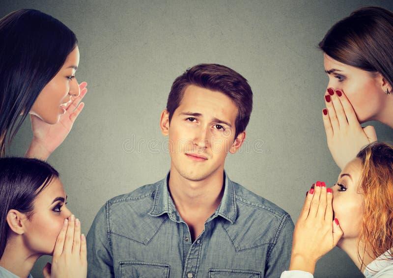 Vrouwen die een geheime recentste roddel fluisteren aan een bored geërgerde man stock fotografie