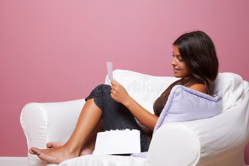 Vrouwen die in een leunstoel worden gezeten die een brief leest royalty-vrije stock afbeelding