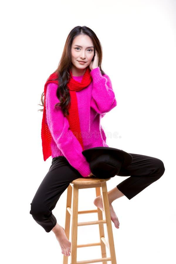 Vrouwen die een roze maniersweater dragen, die op een houten stoel zitten royalty-vrije stock afbeelding