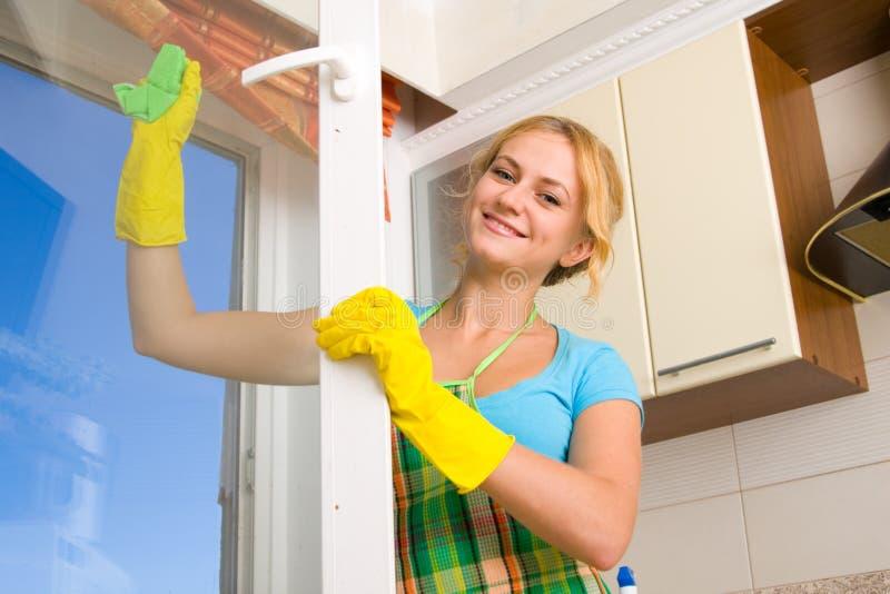 Vrouwen die een venster schoonmaken stock afbeeldingen