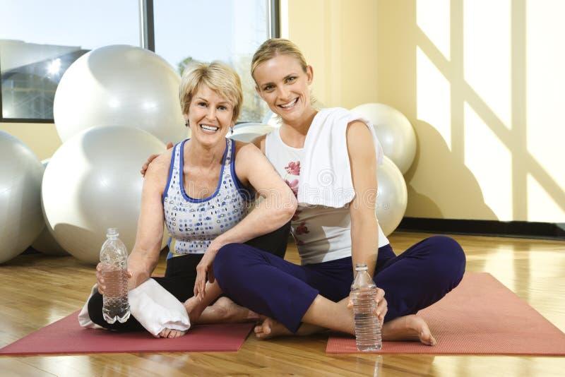 Vrouwen die en bij Gymnastiek zitten glimlachen stock foto's