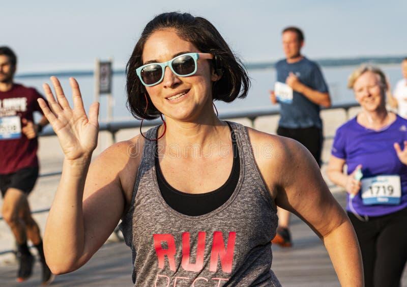Vrouwen die en tijdens lopend ras op promenade glimlachen golven bij strand stock afbeelding