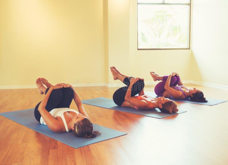 Vrouwen die en zich in Yogaklasse uitrekken ontspannen stock foto