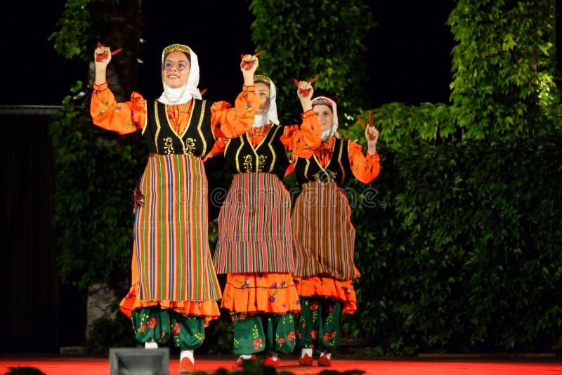 Vrouwen die gebruikend houten lepels in het stadium van het folklorefestival dansen stock afbeeldingen