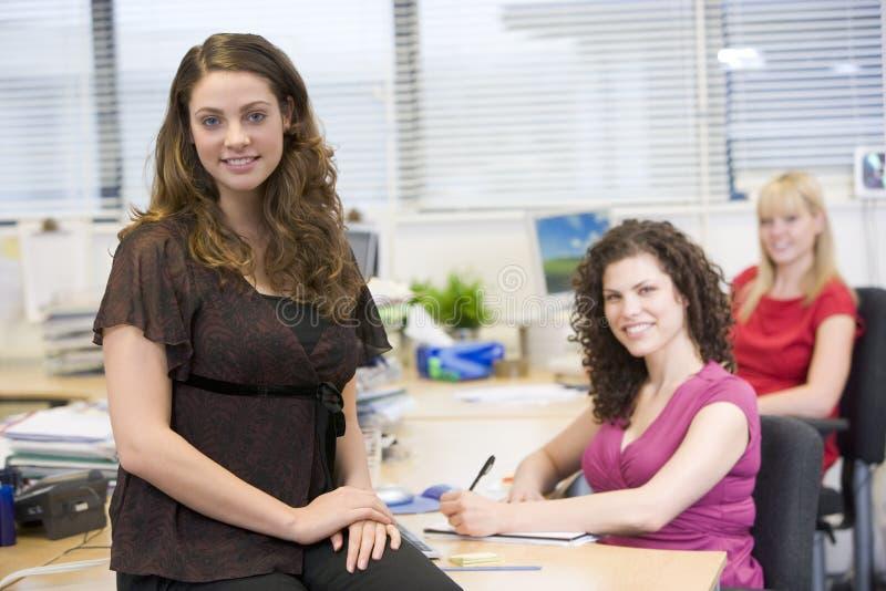 Vrouwen die gelukkig in een bureau werken stock afbeeldingen