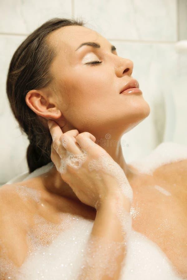 Vrouwen die in haar bad ontspannen stock foto's