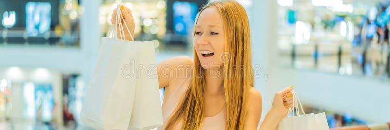 Vrouwen die heel wat het winkelen zakken in vage winkelcomplexbanner dragen, LANG FORMAAT royalty-vrije stock foto's