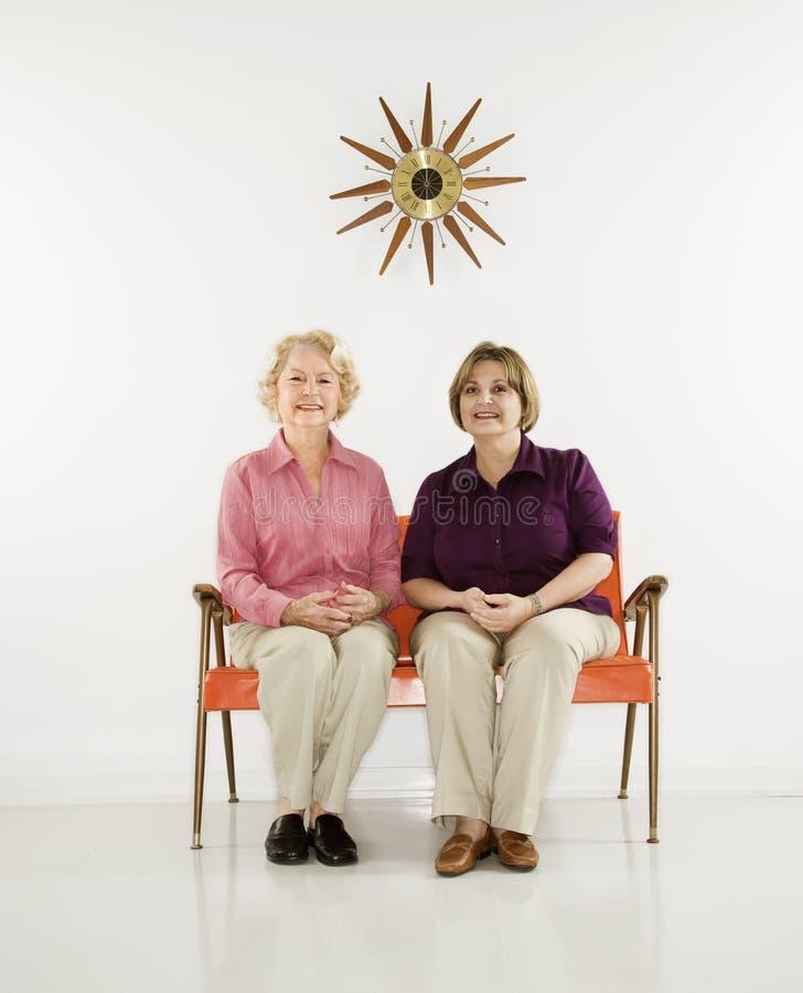 Vrouwen die het glimlachen zitten. stock afbeelding