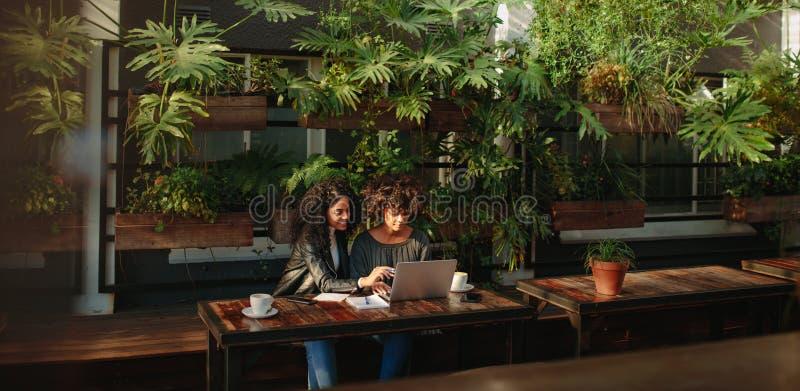 Vrouwen die het werk over koffie bespreken stock fotografie