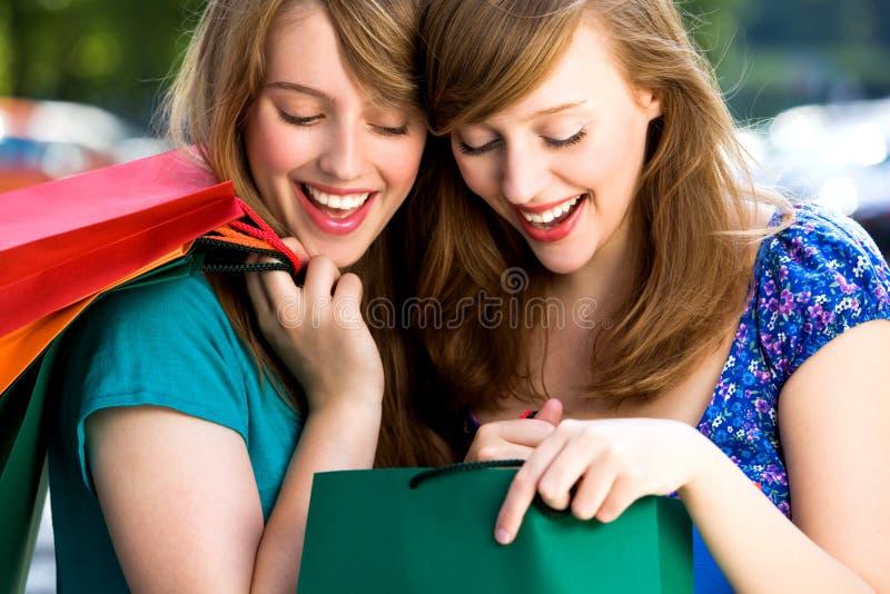 Vrouwen die in het winkelen zakken kijken stock foto