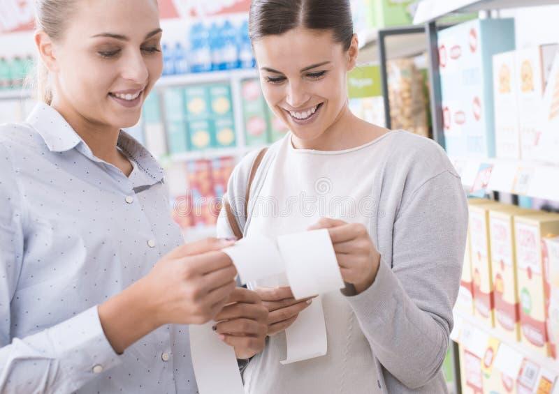 Vrouwen die hun kruidenierswinkelontvangstbewijzen vergelijken royalty-vrije stock foto