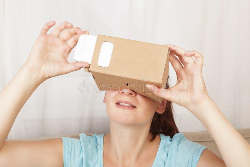 Vrouwen die karton virtuele werkelijkheid gebruiken stock afbeeldingen