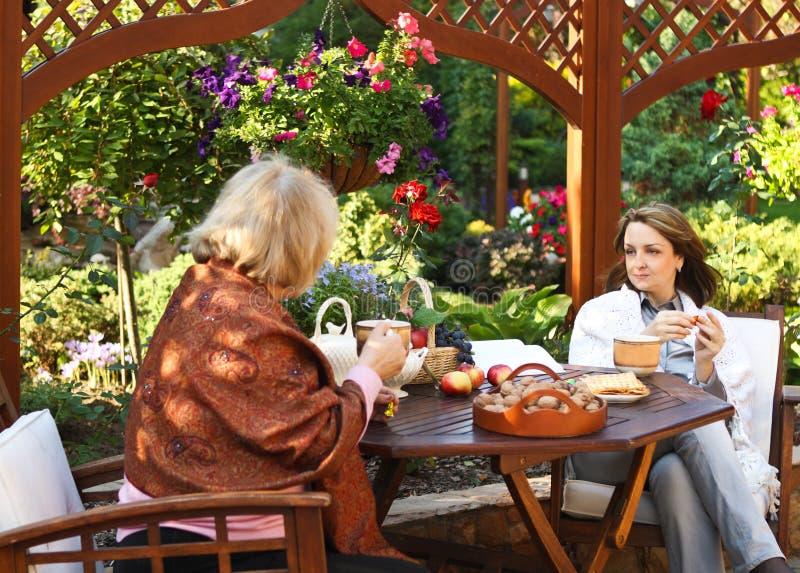 Vrouwen die koffie in een tuin in openlucht drinken stock afbeeldingen