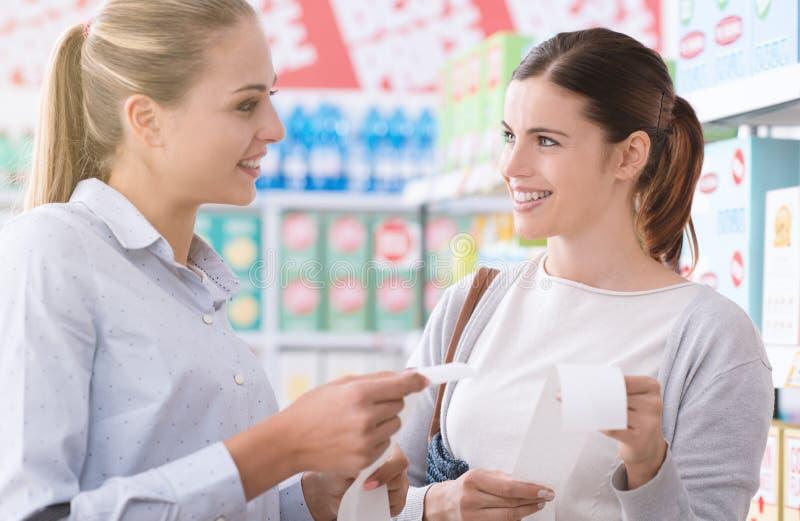 Vrouwen die kruidenierswinkelontvangstbewijzen vergelijken royalty-vrije stock foto